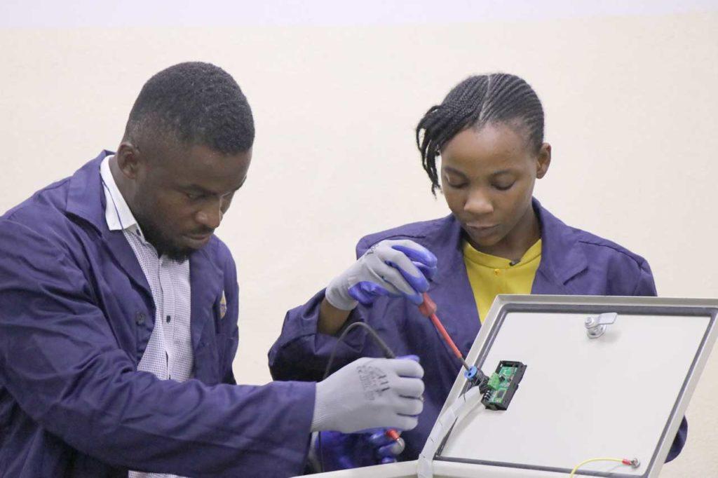 Taiwo Akinjo (right) working on a solar inverter during her internship, Lagos.